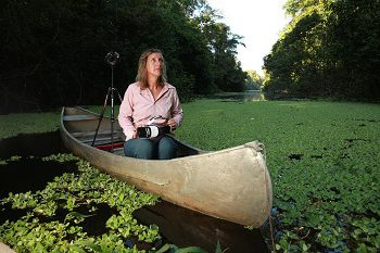 Kerrie Mengersen in a canoe on a river, holding a VR headset
